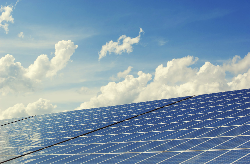 solar panels in the foreground and a blue sky with clouds in the background